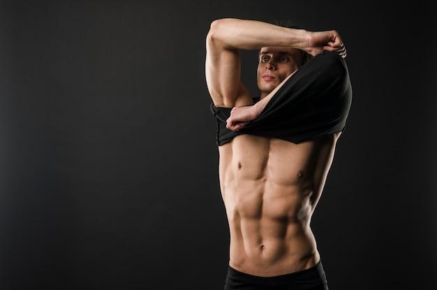 Athletischer mann mit muskeln, der t-shirt mit kopienraum entfernt