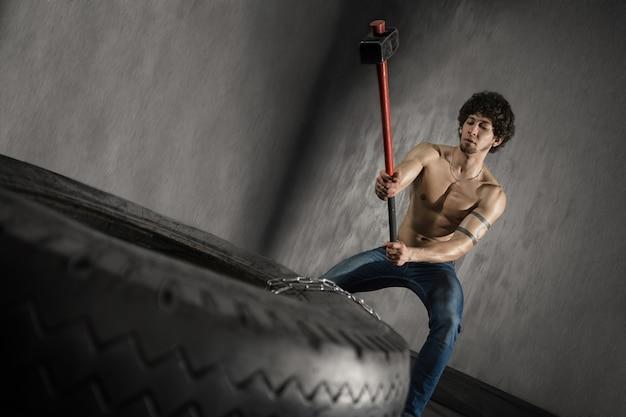Athletischer mann schlägt reifen - training an der turnhalle mit hammer