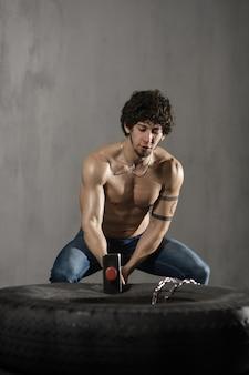 Athletischer mann schlägt reifentraining an der turnhalle mit hammer