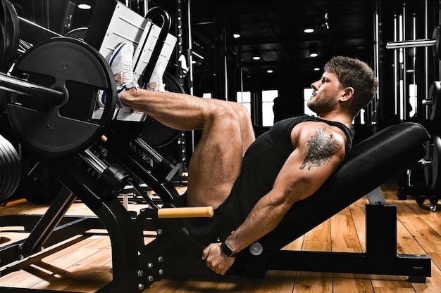 Athletischer mann trainiert beine auf dem simulator in der turnhalle mit gewicht. athletischer körper, gesunder lebensstil, fitnessmotivation, körper positiv.