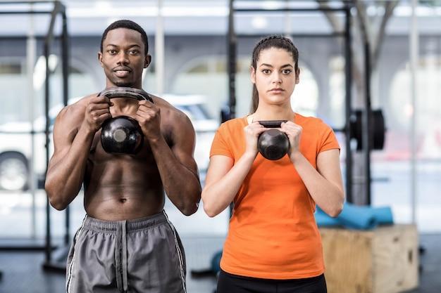 Athletischer mann und frau, die an crossfit turnhalle ausarbeitet