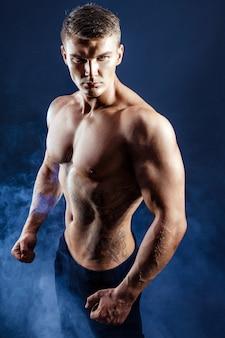 Athletischer mannbodybuilder der hübschen energie. muskulöser körper der eignung auf dunkler rauchszene. perfekter mann. fantastischer bodybuilder, tätowierung, werfend auf.