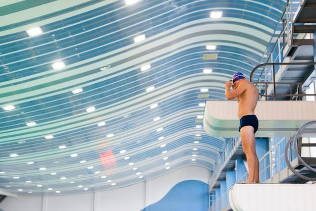 Athletischer mannschwimmer, der sich vorbereitet zu springen