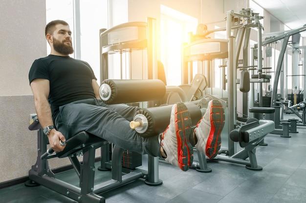 Athletischer muskulöser bärtiger trainierender mann an der modernen sportturnhalle