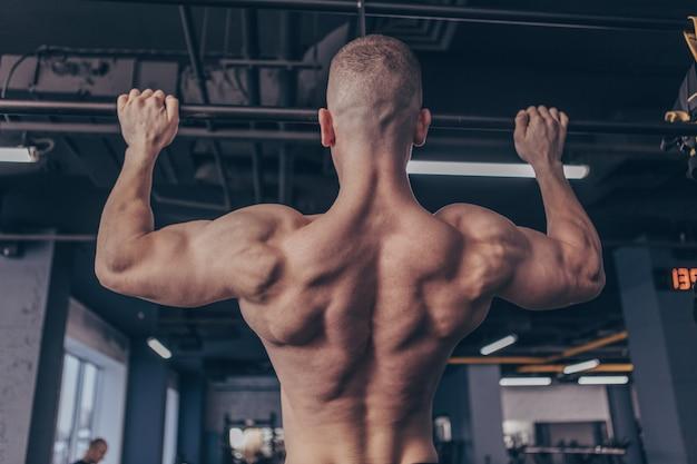 Athletischer muskulöser mann, der an der turnhalle trainiert