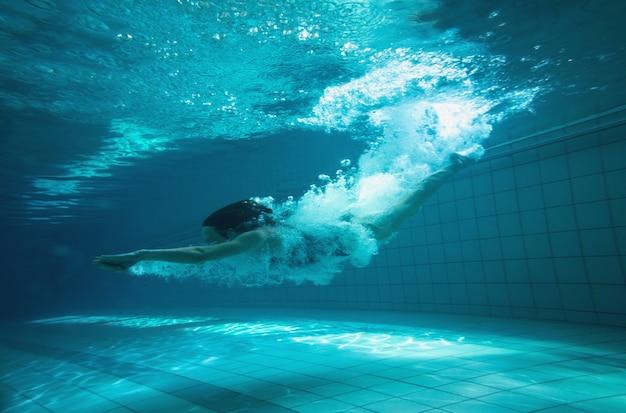 Athletischer schwimmer, der an der kamera unterwasser im swimmingpool in der freizeitmitte lächelt