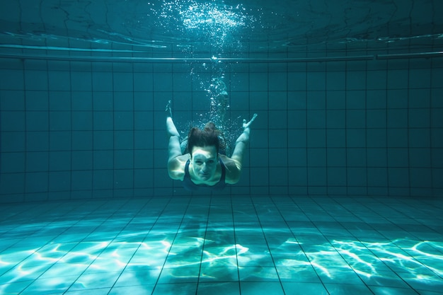 Athletischer schwimmer, der unter wasser an der kamera lächelt
