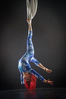 Athletischer sexy luftzirkuskünstler mit rotschopf im blauen kostüm, das tricks auf der luftseide macht.
