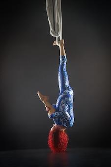 Athletischer sexy luftzirkuskünstler mit rotschopf im blauen kostüm, der tricks auf der luftseide macht.