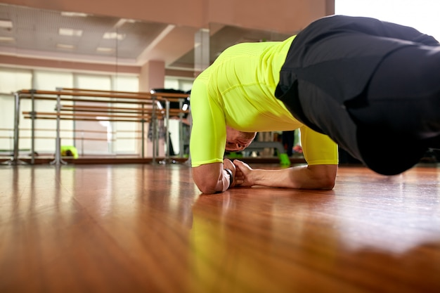 Athletischer sportlicher mann, der plankenübung in der turnhalle tut