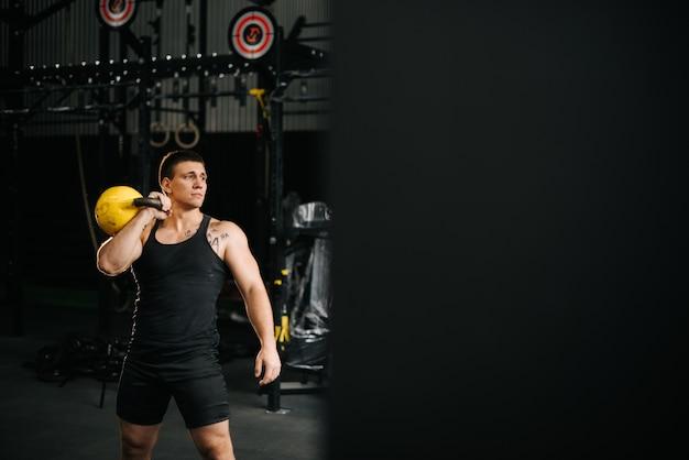 Athletischer starker mann mit perfektem, schönem körper, der sportkleidung trägt, die schwere freie gewichte hebt