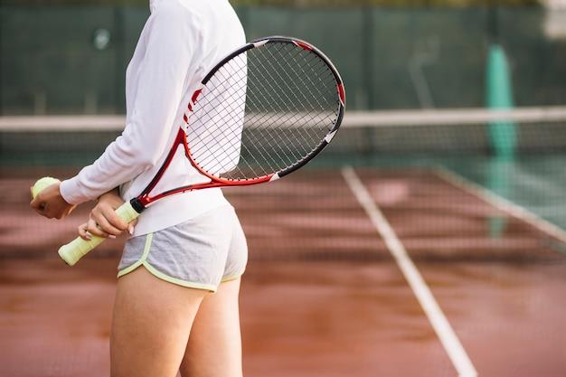 Athletischer tennisspieler, der versucht, die kugel zu schießen