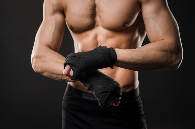 Athletischer torso des muskulösen mannes mit boxhandschuhen