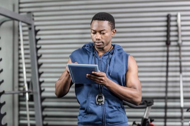 Athletischer trainer, der digitale tablette an crossfit turnhalle verwendet