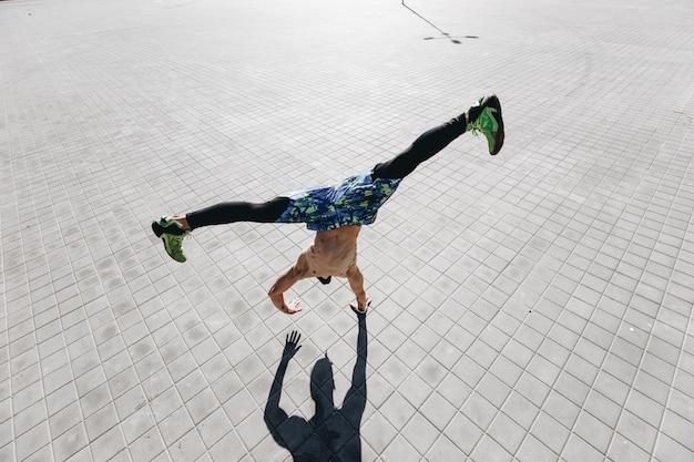 Athletischer typ mit nacktem oberkörper mit tätowierungen, gekleidet in die schwarzen leggings und blauen shorts, der den trick macht, der mit einer hand auf den pflastersteinen auf der straße steht.