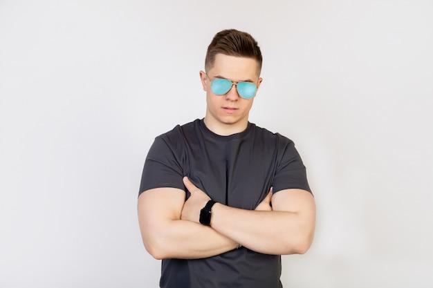 Athletischer typ mit sonnenbrille. der junge mann mit sonnenbrille, der missbilligend die stirn runzelt, hält die hände gefaltet