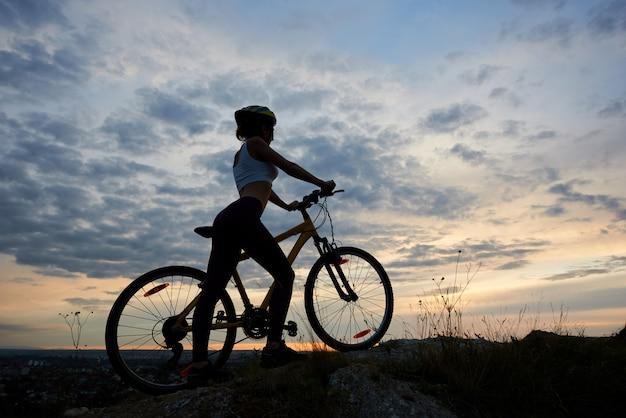 Athletischer weiblicher radfahrer mit fahrrad auf felsen unter schönem abendhimmel mit wolken