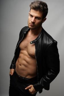 Athletisches junges hispanisches männliches model, das eine schwarze lederjacke trägt und gegen eine graue wand posiert