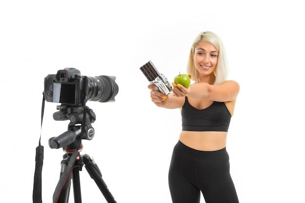 Athletisches mädchen in einer sportuniform zeigt äpfel und schokolade auf einer kamera