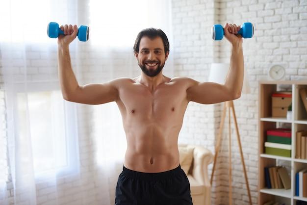 Athletisches manntraining mit muskeln durch dummköpfe oben pumpen.