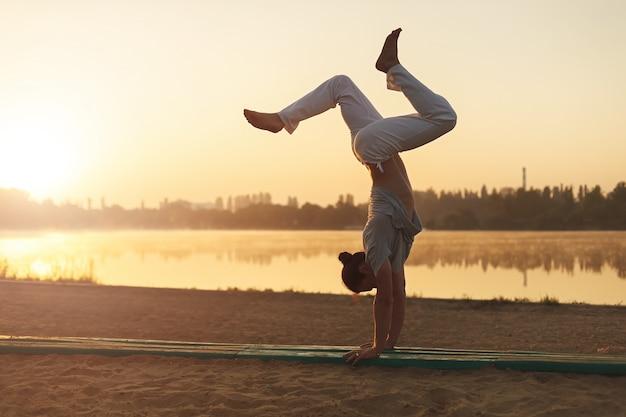 Athletisches yogamann-trainingstraining auf dem strandsonnenaufgang