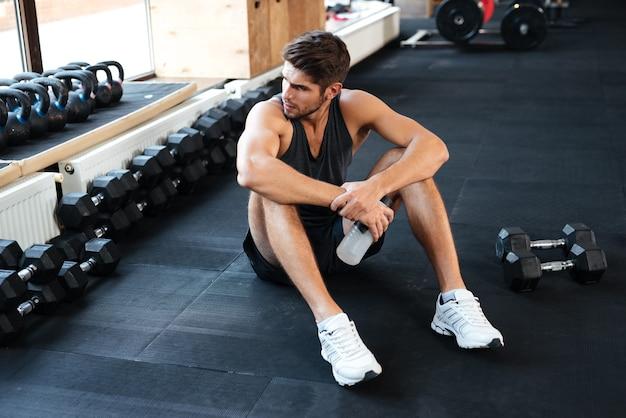 Atletischer mann, der sich im fitnessstudio hinsetzt und wegschaut