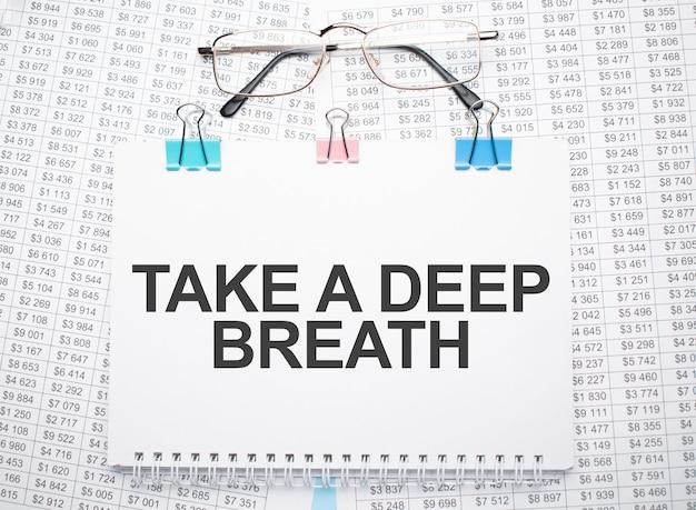 Atmen sie tief durch auf papier geschriebenen text mit stift und brille