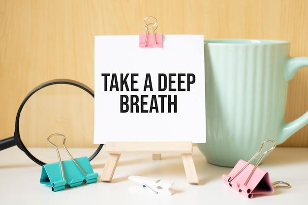 Atmen sie tief durch, geschrieben auf einem schwarzen notizbuch mit lupe und einem stift. geschäfts- und leistungskonzept.