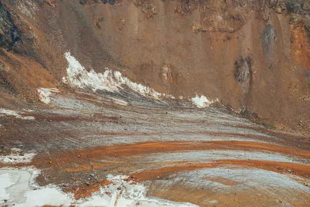 Atmosphärische alpenlandschaft mit wunderschöner gletscherzunge, bedeckt mit steinen und felsigen berghängen