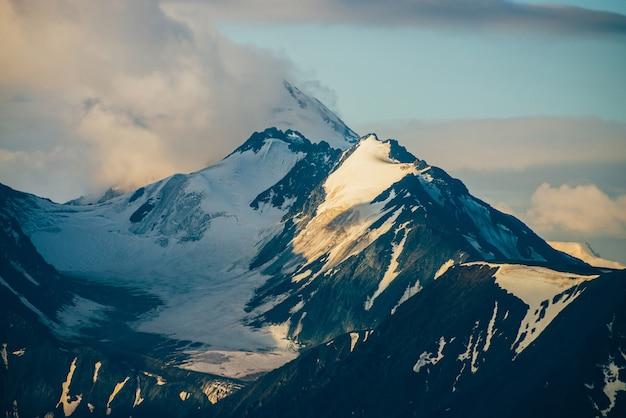 Atmosphärische alpine landschaft mit großen schneebedeckten bergen unter niedrigen wolken in der goldenen stunde
