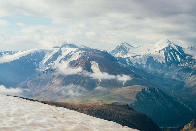 Atmosphärische alpine landschaft mit schnee auf dem gipfel und großen schneebedeckten bergen.