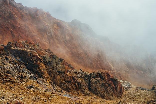 Atmosphärische alpine landschaft mit schroffen bergen innerhalb der wolken. wunderbare hochlandlandschaft mit felsiger wand innerhalb der wolke. schöne felsen über dem abgrund mit dicken wolken. spitziger felsiger gipfel in niedriger wolke