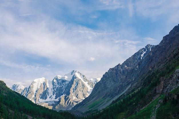 Atmosphärische landschaft mit großem schneebedeckten berggipfel und wald an hängen