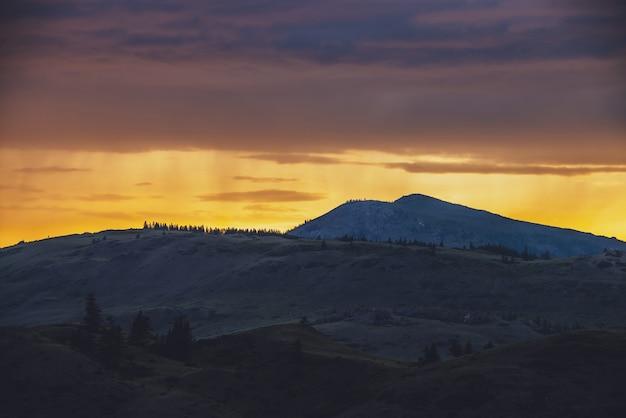 Atmosphärische landschaft mit silhouetten von bergen mit bäumen auf dem hintergrund des lebendigen orange-blau-lila morgenhimmels. bunte naturlandschaft mit sonnenuntergang oder sonnenaufgang in leuchtender farbe. sundown paysage.