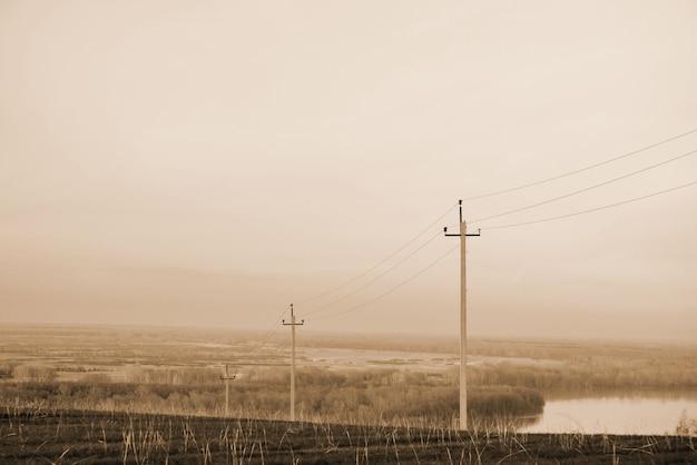 Atmosphärische landschaft mit stromleitungen auf dem gebiet auf hintergrund von fluss unter sepiahimmel.