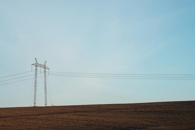 Atmosphärische landschaft mit stromleitungen auf dem gebiet unter blauem himmel.