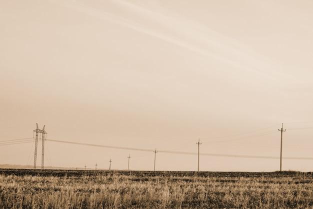 Atmosphärische landschaft mit stromleitungen auf dem gebiet unter himmel in den sepiatönen.