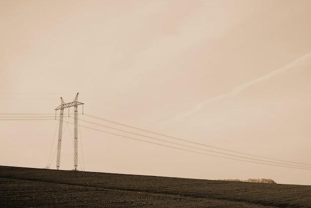 Atmosphärische landschaft mit stromleitungen auf dem gebiet