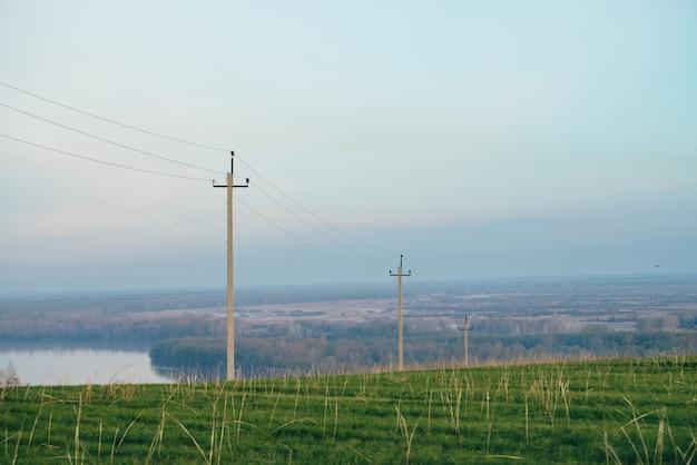 Atmosphärische landschaft mit stromleitungen auf dem grünen gebiet auf hintergrund von fluss unter blauem himmel