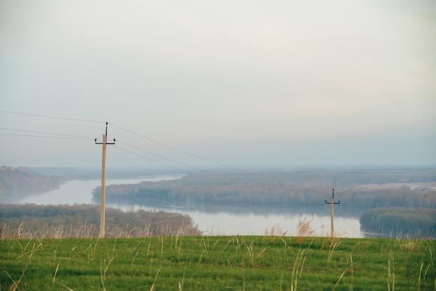 Atmosphärische landschaft mit stromleitungen im grünen feld auf hintergrund des flusses unter blauem himmel. elektrische säulen mit kopierraum.