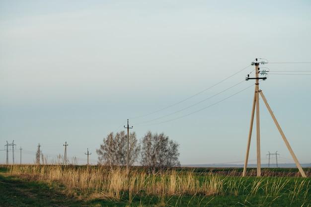 Atmosphärische landschaft mit stromleitungen im grünen feld mit feldweg der bäume unter blauem himmel. elektrische säulen mit kopierraum. hochspannungsdrähte über der erde. elektrizitätswirtschaft.