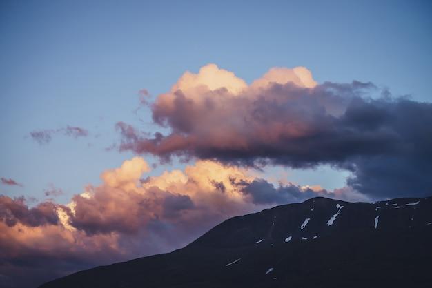 Atmosphärische minimale berglandschaft mit lila morgenhimmel. malerische minimalistische landschaft mit lila sonnenuntergang in den bergen. schöner sonnenaufgang in den bergen in pastelltönen. felsiger berg im bewölkten himmel der morgendämmerung