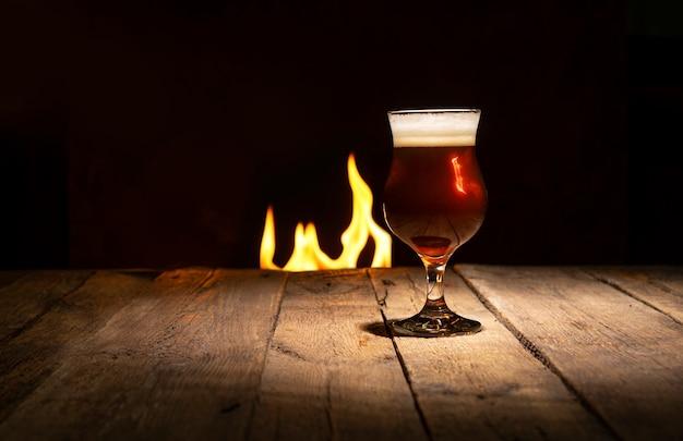 Atmosphärischer abend in einer kneipe. bierglas auf einem dunklen hölzernen hintergrund mit kamin