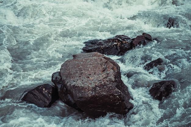 Atmosphärischer naturhintergrund mit riesigen steinen im gebirgsfluss. große felsen in der starken wasserstromnahaufnahme. naturkulisse mit großen felsbrocken in wellen. dunkler türkisfarbener bergfluss mit steinen.