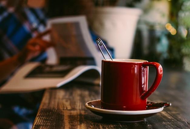 Atmosphärisches foto mit rotem becher auf holztisch im café auf dem ba