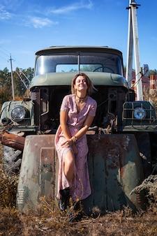Atmosphärisches lebensstilfoto des porträts im freien der jungen schönen dunkelhaarigen frau in einem rosa kleid in einem blumendruck gegen den hintergrund eines alten lkw-autos
