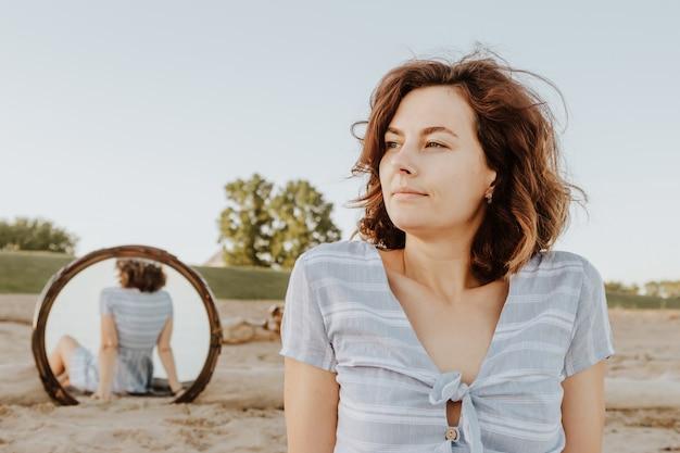 Atmosphärisches lebensstilfoto im freien der jungen schönen dunkelhaarigen frau im sommerkleid, das auf dem strand im spiegelbild aufwirft.
