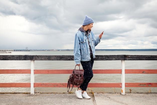 Atmosphärisches lifestyle-foto im freien der jungen schönen dunkelhaarigen frau in strickmütze