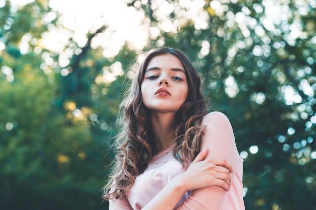 Atmosphärisches porträt der jungen schönen frau langes haar und lässiges make-up in der natur