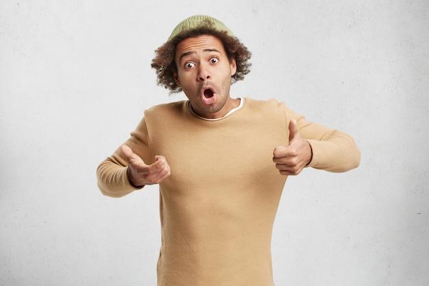 Atonished mann trägt einen braunen pullover und einen trendigen hut, öffnet den mund weit,